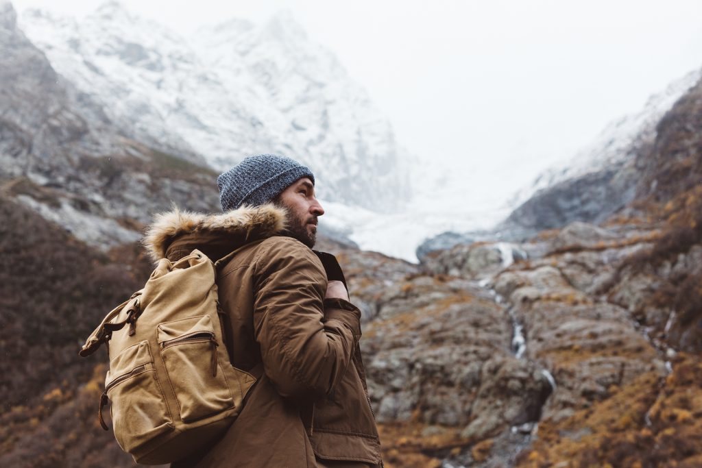 A man with outdoor gear is out for a hike.