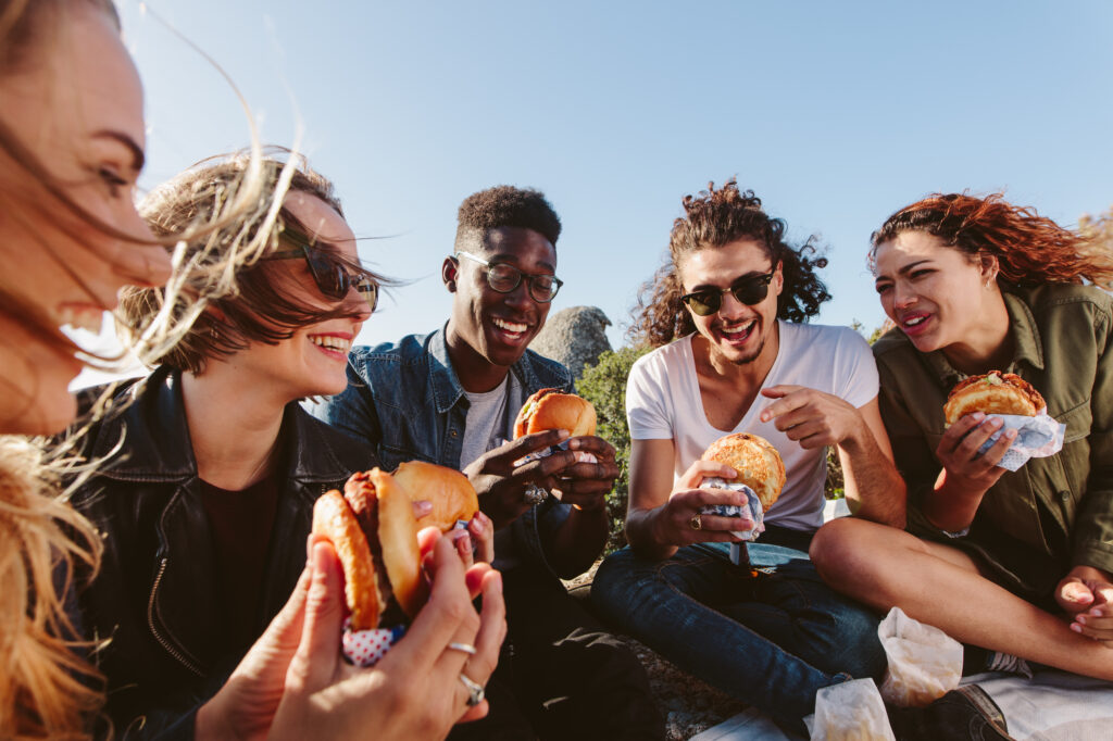 A group of friends enjoy takeout outside.